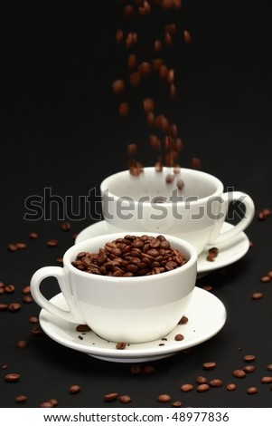 Two white cups and crumbling coffee beans