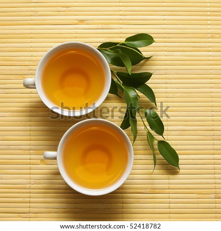 Two white cups and green branch on the mat. Series - stock photo