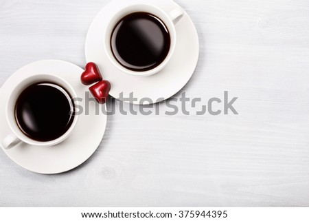 Two white cups of black coffee with two chocolate heart - shaped red sweets. White wooden background. Drinking coffee with love and happy Valentine's day concept.