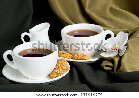 Two white cups of tea and cookies with sesame seeds on a background of silk fabric