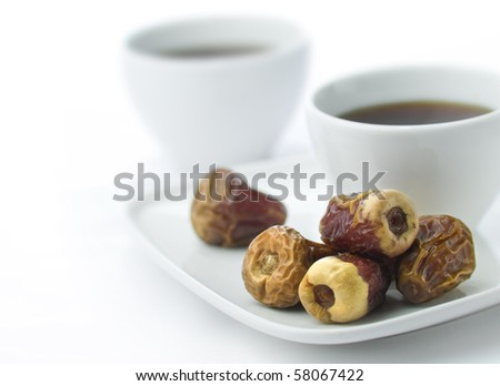 Two white cups with black coffee with dates at foreground - stock photo