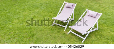 Two white deck chairs in the garden