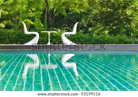 Two white deck chairs side swimming pool. - stock photo