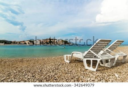 Two white deckchairs on a beautiful beach in Croatia, Primosten - stock photo