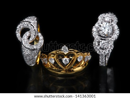 Two white diamond rings and one golden diamond ring on black background - stock photo