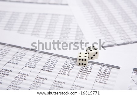 two white dice on the financial sheet