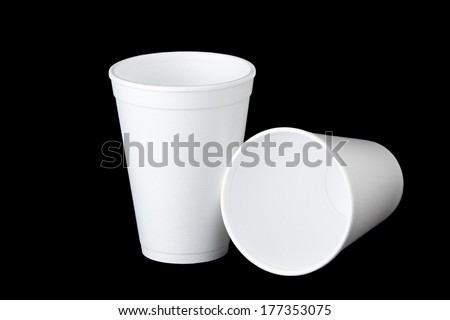Two white empty styrofoam cups on black background. One stands upright and the second cup lays next to the first. - stock photo