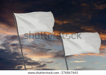 Two white flags over a cloudy sky after storm at sunset. Peace on war symbol - stock photo