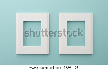 two white frames on the blue wall - stock photo