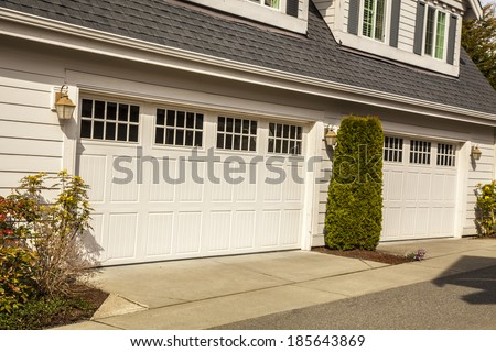 Two white garage doors with windows - stock photo