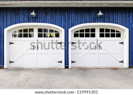 Two white garage doors with windows on blue house - stock photo