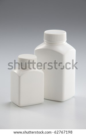 Two white medicine bottle closed on plain background - stock photo