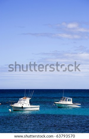 two white motor boats on blue sea under summer sky