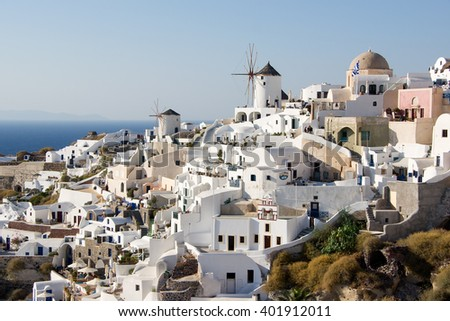 Two white old mills on a background of white  houses in the town of Oia on Santorini island in Greece     - stock photo