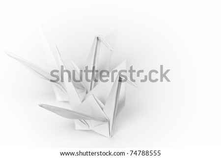 Two white paper birds next to each other on a white background. Shallow depth of field. - stock photo