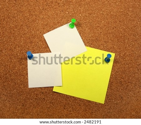 Two white papers and a yellow paper attached to a corkboard. - stock photo