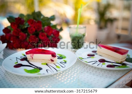 Two white plates with cut pieces of cherry pie on the table is a bouquet of red roses, with a glass of drink. Preparations for a romantic rendezvous at a cafe restaurant bar club. Luxury life style  - stock photo