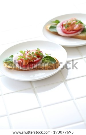 Two white plates with open faced sandwiches on them. - stock photo