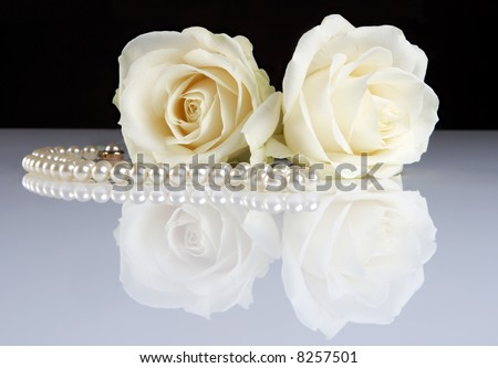 Two white roses reflected on a white surface, and a pearl necklace - stock photo
