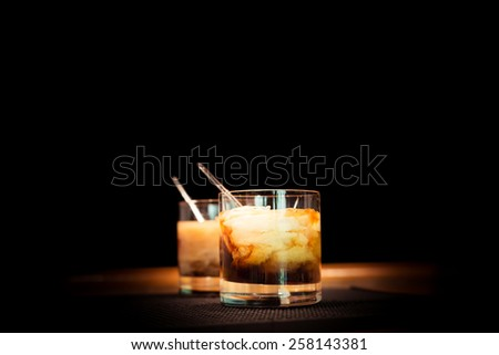 Two white russian cocktails on the bar stand on rubber mat. Shallow DOF and marsala tonned - stock photo