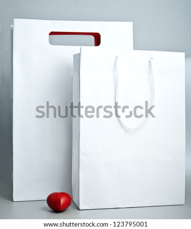 two white  shopping bag and red decorative heart - stock photo
