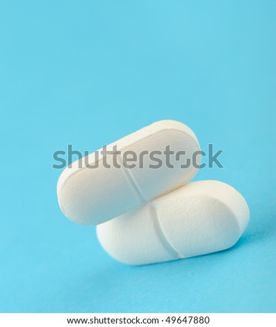 Two white tablet on a blue background. A photo close up