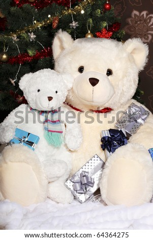 Two white teddy bears sitting at the Christmas tree with presents