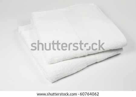 Two white towels on neutral background.