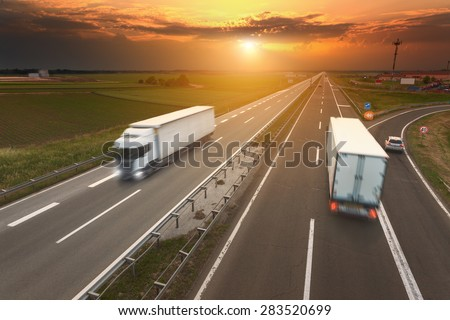 Two white trucks driving in motion blur on the freeway towards the setting sun. Rush hour on the motorway near Belgrade - Serbia. - stock photo