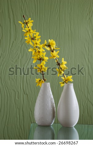 Two white vases with  branch and yellow flowers over green background - stock photo