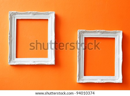 Two white vintage frames on orange wall - stock photo