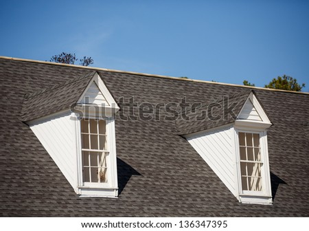 Two white wood dormers on a grey shingle roof under blue sky - stock photo