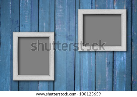 Two white wood picture frame on Blue color paint plank wall for background - stock photo