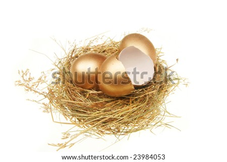 Two whole and one broken golden eggs in a straw nest