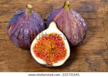 Two whole and one half fresh figs on old rustic wooden board - stock photo