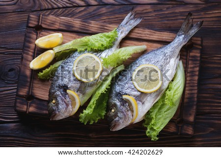 Two whole baked dorados in a rustic wooden setting, top view - stock photo