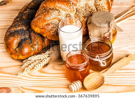 Two whole fresh challah bread with poppy and sesame on a wooden background