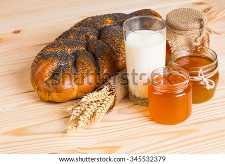 Two whole fresh challah bread with poppy and sesame seeds and honey wooden background