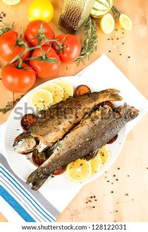 Two Whole Trouts Fried in Pan and Served with Tomatoes and Sweet Potatoes - stock photo