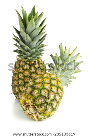 Two whole uncut pineapple fruit (ananas comosus) with green leaves over white background - stock photo