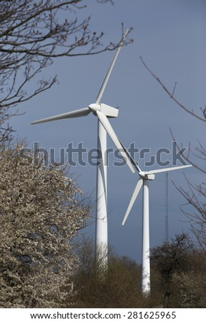 two wind power plants among trees - stock photo