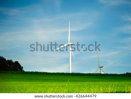 Two wind turbines - environmental protection eco tower generating electricity in green field with storm clouds in the bacground - stock photo