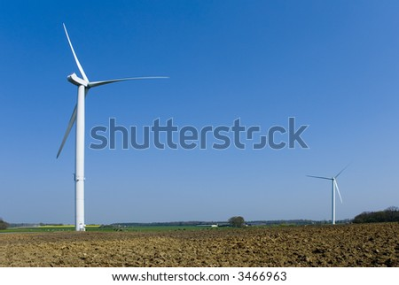 Two wind turbines in country. Empty space in upper right corner on blue sky background. - stock photo