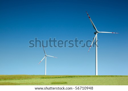 two wind turbines on green field