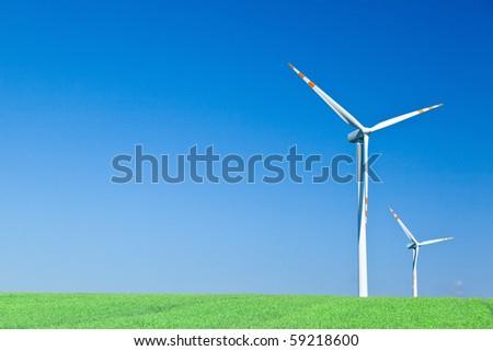two wind turbines on green field - stock photo