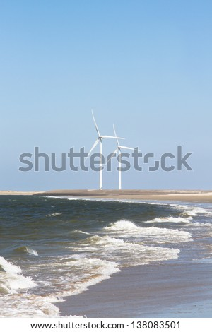 Two wind turbines on the horizon of a beach where the waves of the sea roll on. - stock photo