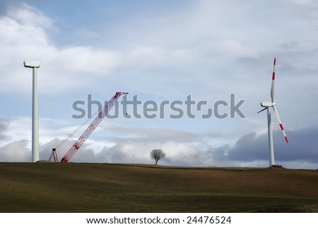 Two wind turbines, one complete and one under construction - stock photo