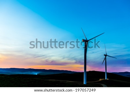 Two wind turbines standing together in the dusk twilight against the colorful sky