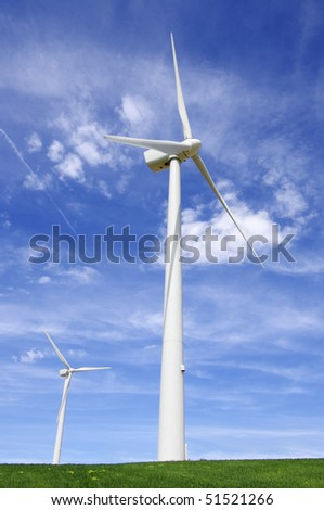 two windmills in a green meadow with blue sky