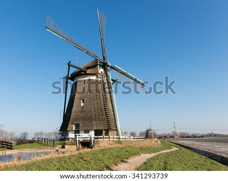 Two windmills in a row in polder near Zevenhuizen in the province of South Holland, Netherlands - stock photo